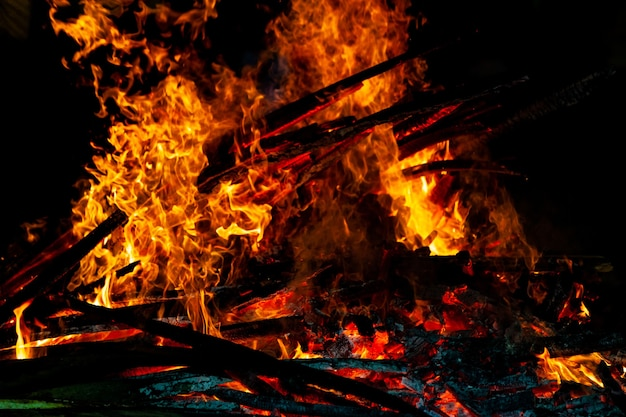 Falò che brucia su uno sfondo scuro, fiamma a legna.