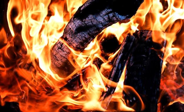 Falò con close-up di legna da ardere carbonizzata, sfondo su uno sfondo nero