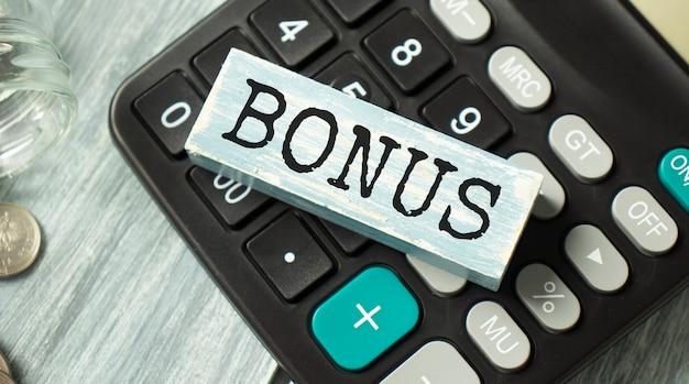 Parola bonus realizzata con blocchi di costruzione sulla calcolatrice Foto Premium