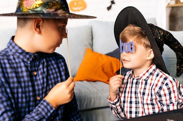 Boo ritratto di due piccoli mostri che si nascondono dietro maschere in una stanza dipinta di halloween a casa
