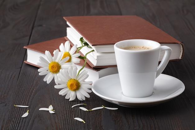 Il libro e la margherita fioriscono sulla tavola di legno