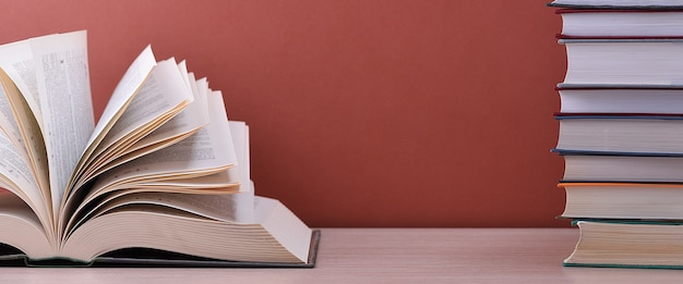 Il libro è aperto, sdraiato sul tavolo vicino a una pila di libri