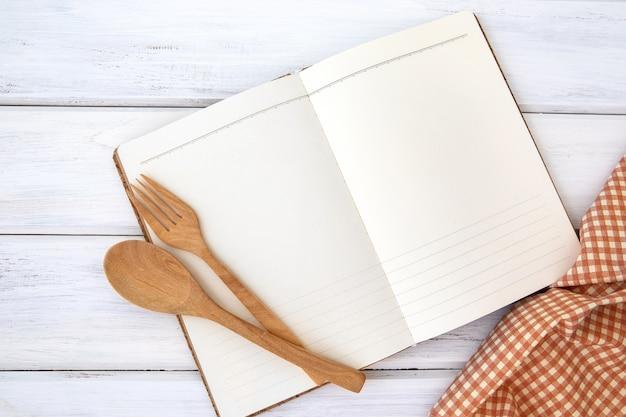 Libro blocco note di carta e tovaglia con forchetta in legno e cucchiaio sul tavolo bianco