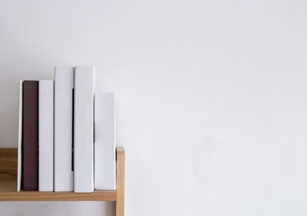 Spine del libro in bianco dello scaffale, pila legante vuota su legno