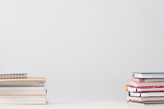 Pile di libri sulla scrivania sopra bianco.