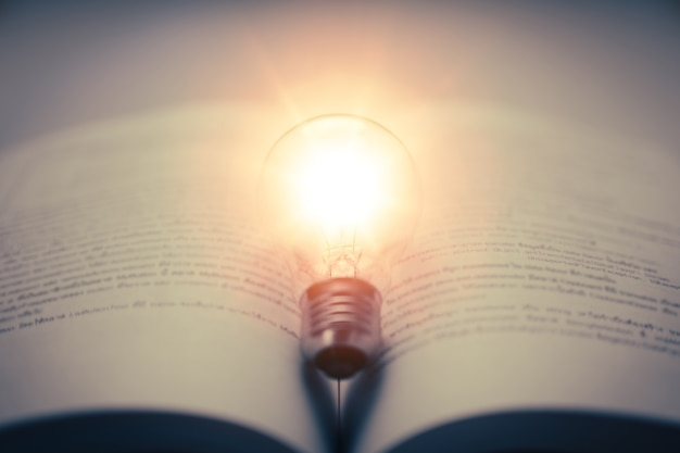 Prenota con una lampadina incandescente apprendimento autonomo o conoscenza dell'istruzione e concetto di studio aziendale