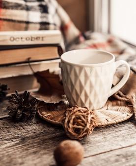 Prenoti con la sciarpa e la tazza di tè su fondo di legno