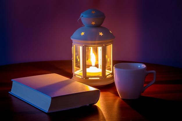 Un libro con una copertina bianca vicino alla lanterna e una tazza di caffè la sera