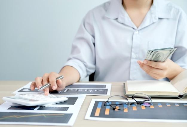 Il contabile usa la calcolatrice e il laptop facendo il conto per pagare le tasse sulla scrivania bianca in ufficio.