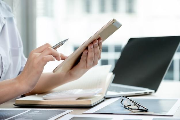 Il contabile usa tablet e laptop facendo conto per pagare le tasse sulla scrivania bianca in ufficio.