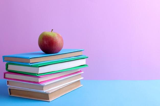 Libri e una mela su uno sfondo blu e rosa.