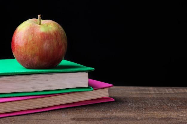 Libri e una mela su un tavolo di legno marrone su sfondo nero. concetto di educazione