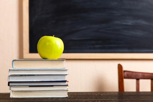 Libri, mela, penne, matite e bicchieri su un tavolo di legno, contro un bordo di gesso.