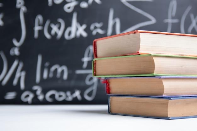 Libri su sfondo lavagna con formule matematiche