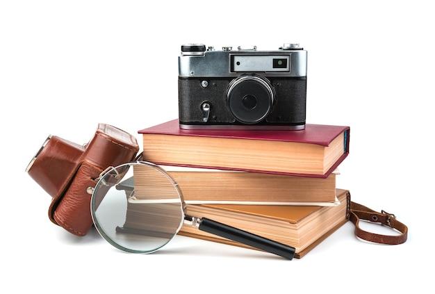 Libri, macchina fotografica e lente d'ingrandimento isolati su priorità bassa bianca. vista laterale.