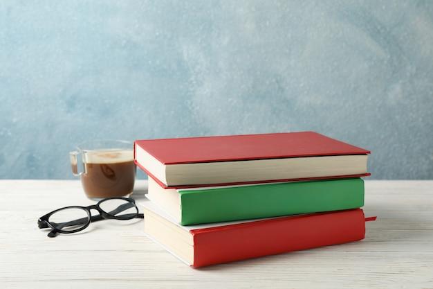 Libri, tazza di caffè e vetri sulla tavola di legno, spazio per testo