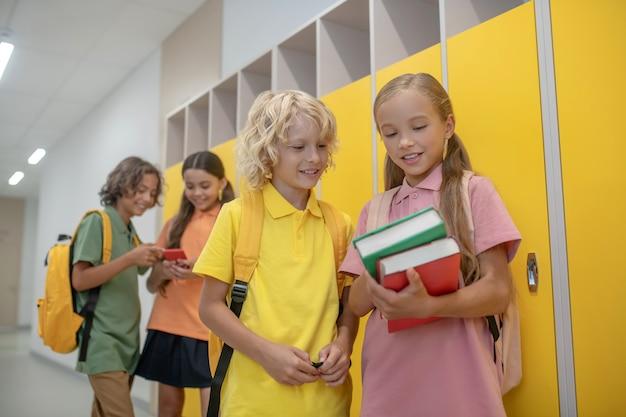 Libri. ragazza carina che mostra i suoi libri al ragazzo biondo in maglietta gialla