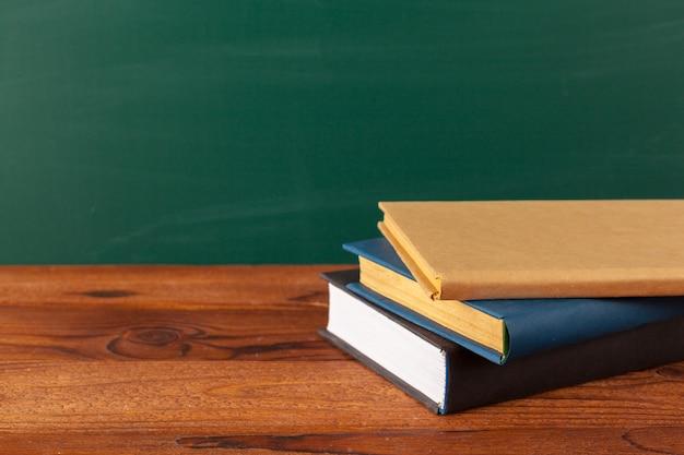 Libri sulla scrivania, lavagna sfondo