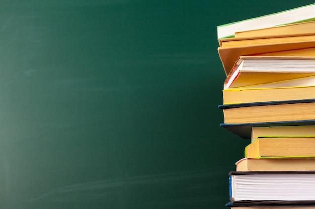 Libri sulla scrivania, sfondo di lavagna