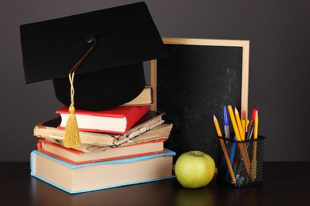 Libri e cappuccio del magister contro il consiglio scolastico sulla tavola di legno su uno spazio grigio