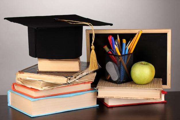 Libri e berretto da maestro contro il consiglio scolastico su un tavolo di legno su grigio