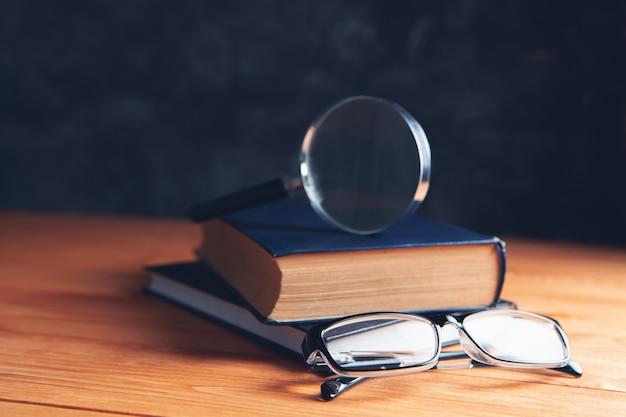 Libri, lente d'ingrandimento e occhiali sul tavolo