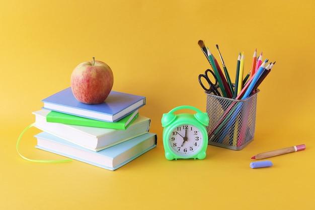 Libri, matite e sveglia su sfondo luminoso, concetto di apprendimento domestico