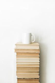 Mucchio di libri e tazza di caffè sulla superficie bianca