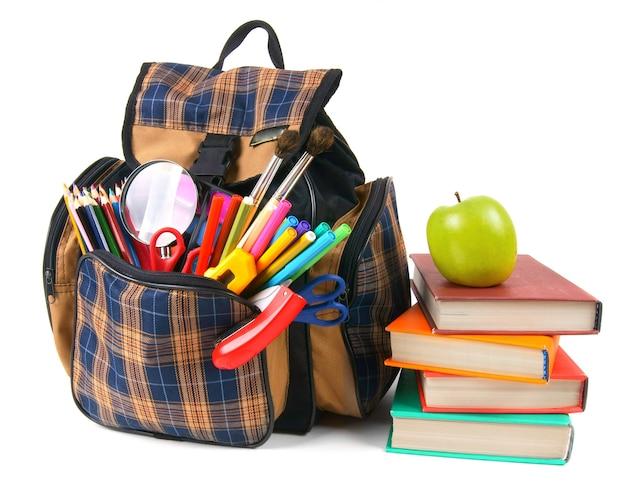 Libri, accessori per la scuola e uno zaino. su uno sfondo bianco.