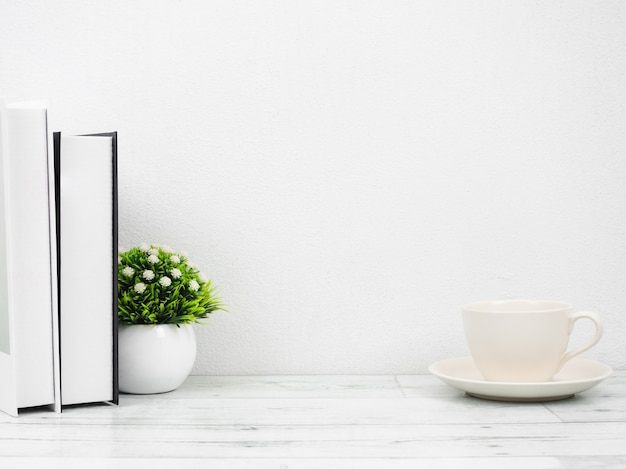 Libri e piccolo vaso sulla parete bianca dello spazio della copia di stile minimo della tavola di legno bianca, spazio di lavoro a casa