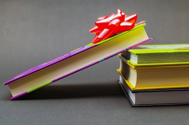 Libri avvolti con nastro adesivo colorato sul tavolo su sfondo scuro. copia spazio.