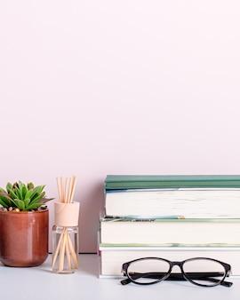 Scaffale con libri multicolori, piante grasse da appartamento e cornice nera per il testo. sfondo per la giornata dell'insegnante, la giornata mondiale del libro. natura morta con pila di libri colorati, lavagna