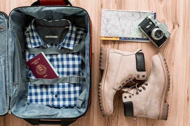 Stivali e fotocamera vicino valigia aperta