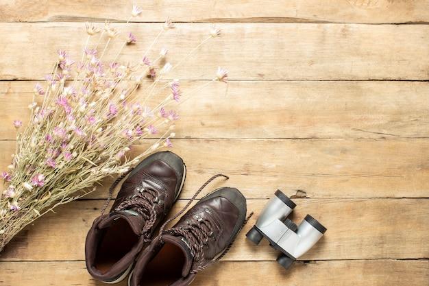 Stivali per trail, binocoli, fiori di campo su fondo in legno. concetto di escursionismo, turismo, campo, montagne, foresta.