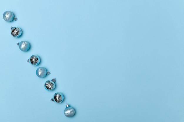 Bordo delle sfere blu della decorazione di natale sul colore di sfondo copia spazio piatto vista dall'alto