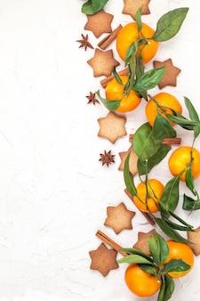 Bordo dei biscotti della stella di natale con spezie e mandarino su fondo bianco con copyspace. vista dall'alto