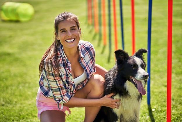 Cane border collie e una donna su un campo di agilità