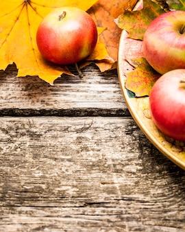Bordo di mele e foglie di autunno sul vecchio tavolo di legno. concetto del giorno del ringraziamento