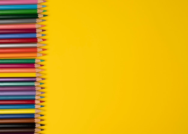 Bordo di matite multicolori isolato su sfondo giallo copia spazio per la vista dall'alto del testo