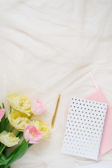 Un bordo di fiori rosa di tulipani gialli, accessori e cosmetici sullo sfondo. disposizione della scrivania dell'ufficio domestico delle donne. disposizione piana, vista dall'alto.