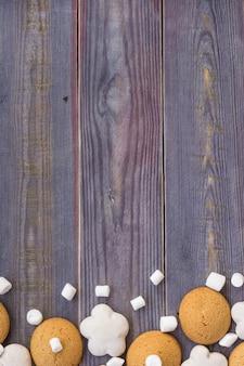 Confine di pan di zenzero bianco e marrone con marshmallow su fondo di legno.