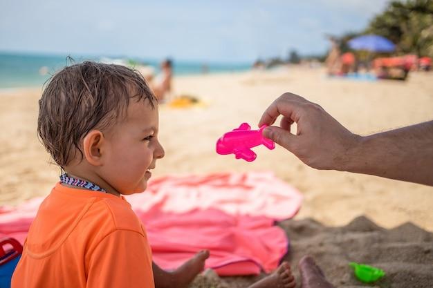 Confini aperti un bambino carino sulla spiaggia guarda un aeroplano giocattolo tenuto da un genitore e ride