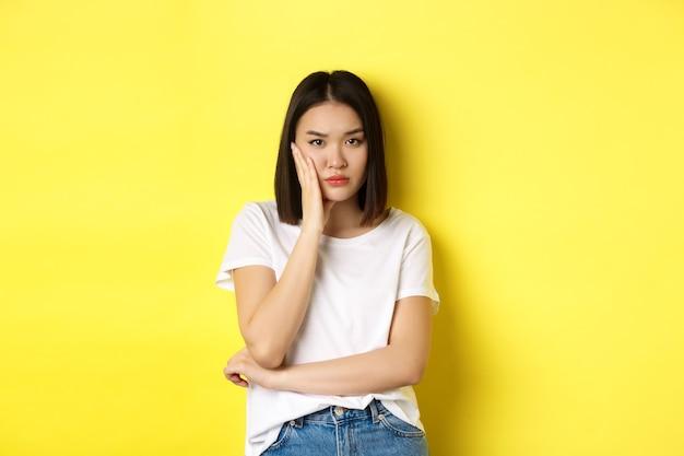 Donna asiatica annoiata e infastidita stanca di ascoltare, guardando scettico alla telecamera, in piedi sul giallo