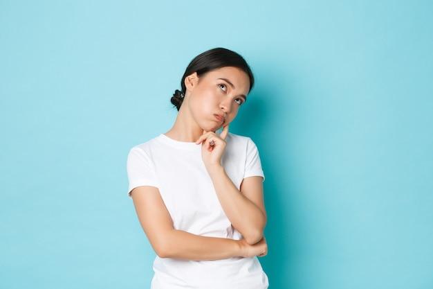 Ragazza asiatica carina annoiata o infastidita in maglietta bianca alza gli occhi al cielo, si appoggia sul palmo e sembra indifferente, non è dell'umore, si sente noia e apatia, in piedi sfondo blu non preoccupato.