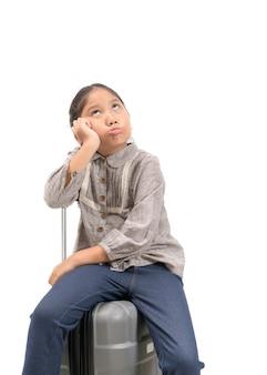 Bambino asiatico annoiato con la valigia isolata