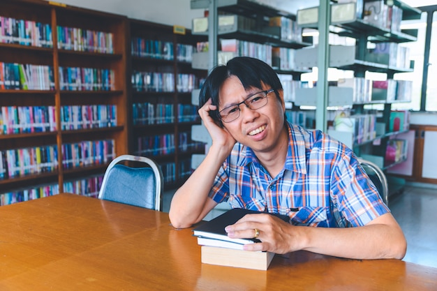 Studente asiatico annoiato con i libri in biblioteca