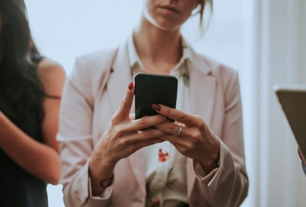 Donna d'affari annoiata che usa il suo telefono