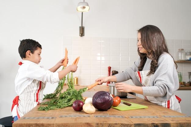 Il bambino annoiato gioca con alcune verdure in cucina mentre la madre cucina un'alimentazione sana
