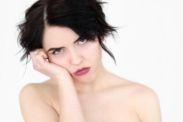 Annoiato stufo donna apatica indifferente sul muro bianco.
