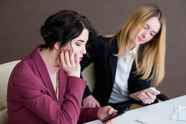 Donne indifferenti annoiate di affari che si siedono nell'ufficio che esamina i loro telefoni.